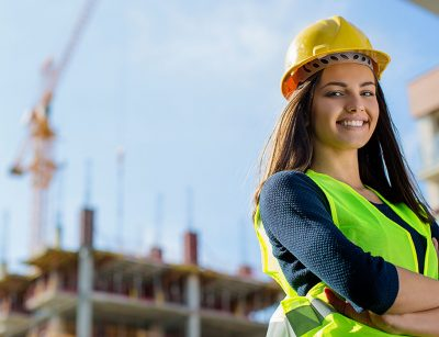 Female engineer stands in front of a building under construction