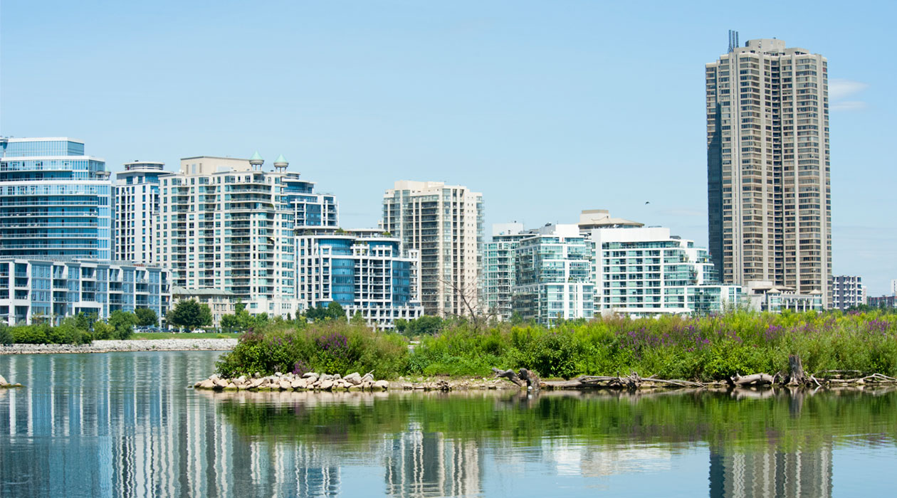 Skyline of condominiums in distance, water and island in front