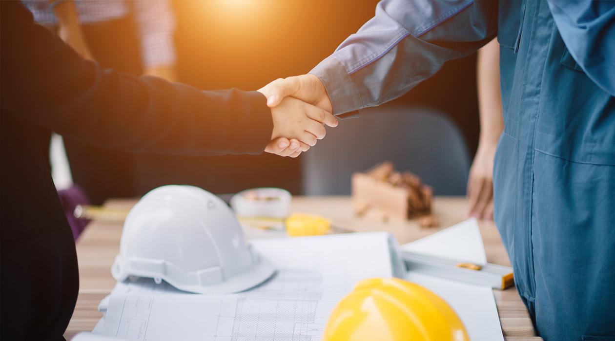 Engineers shaking hands over blueprints
