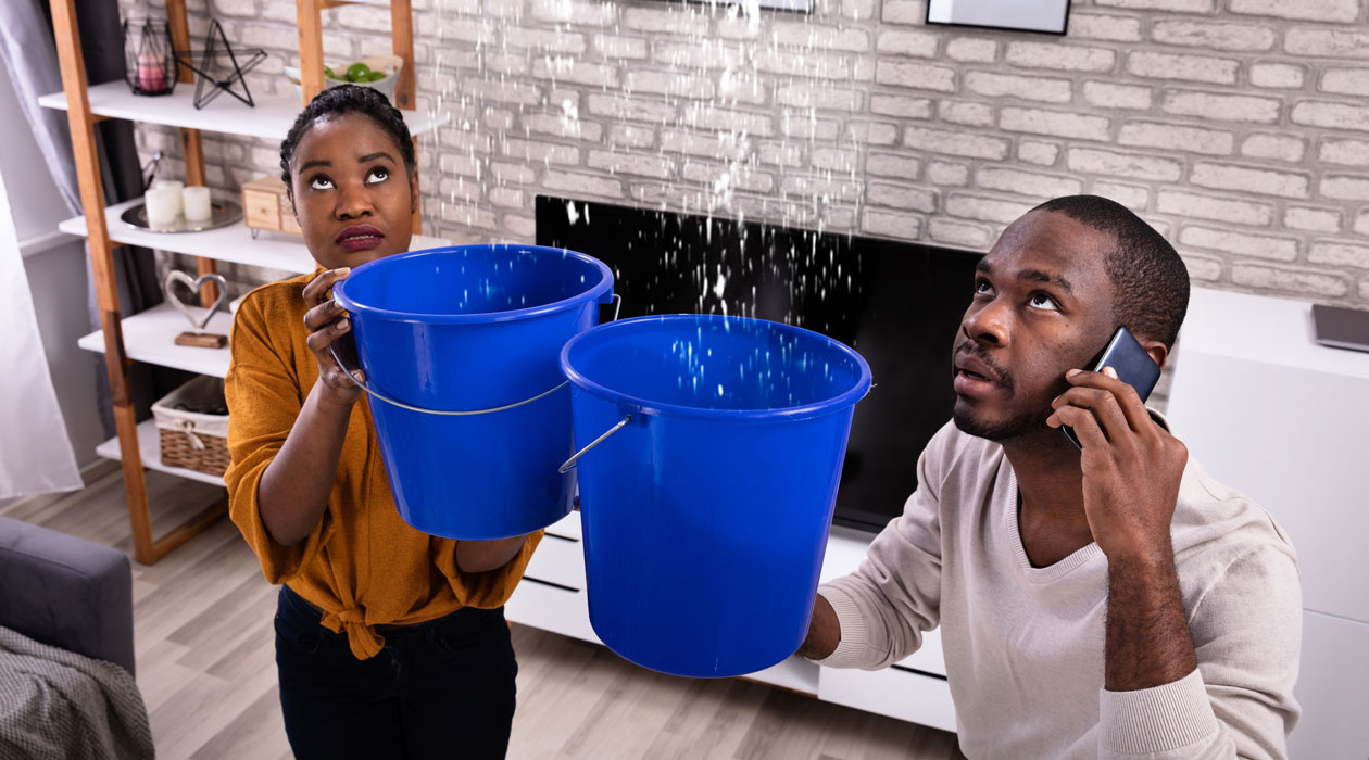 Couple holding buckets to catch water leak from condo above