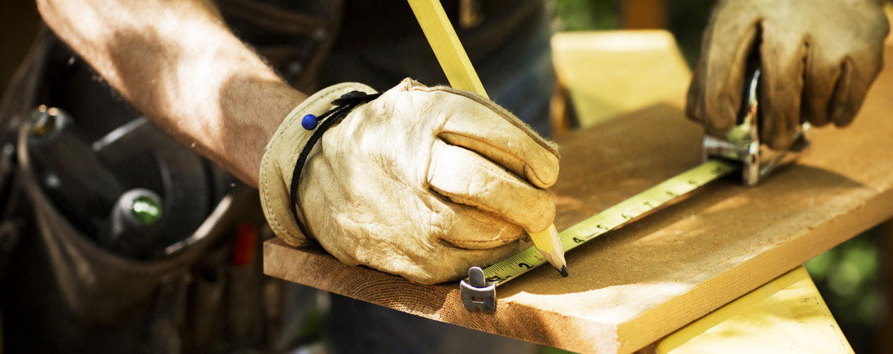 Close up of a builder using a tape measure on a plank of wood