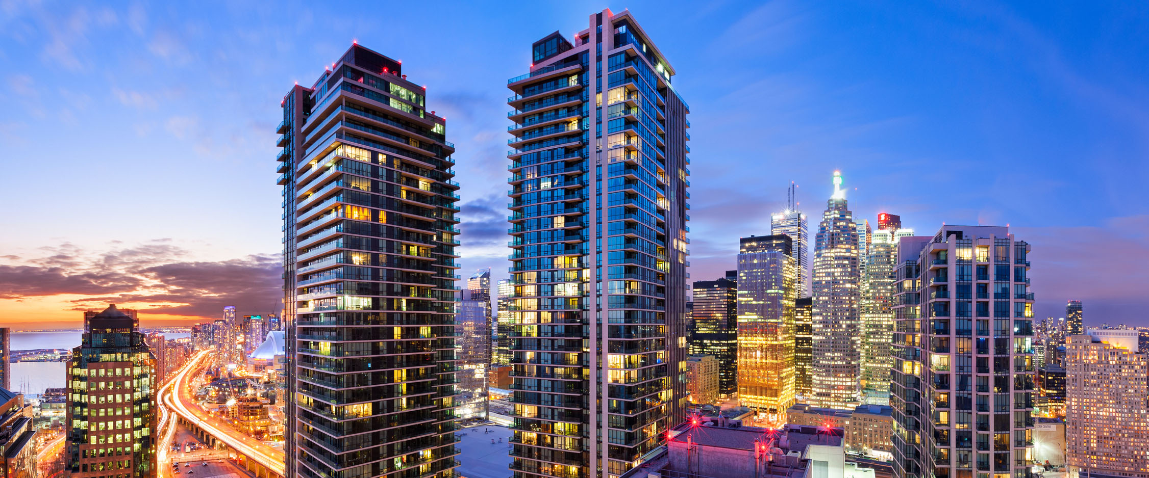 Long exposure panoramic photo of downtown Toronto cityscape and condominium towers at sunset and twilight.