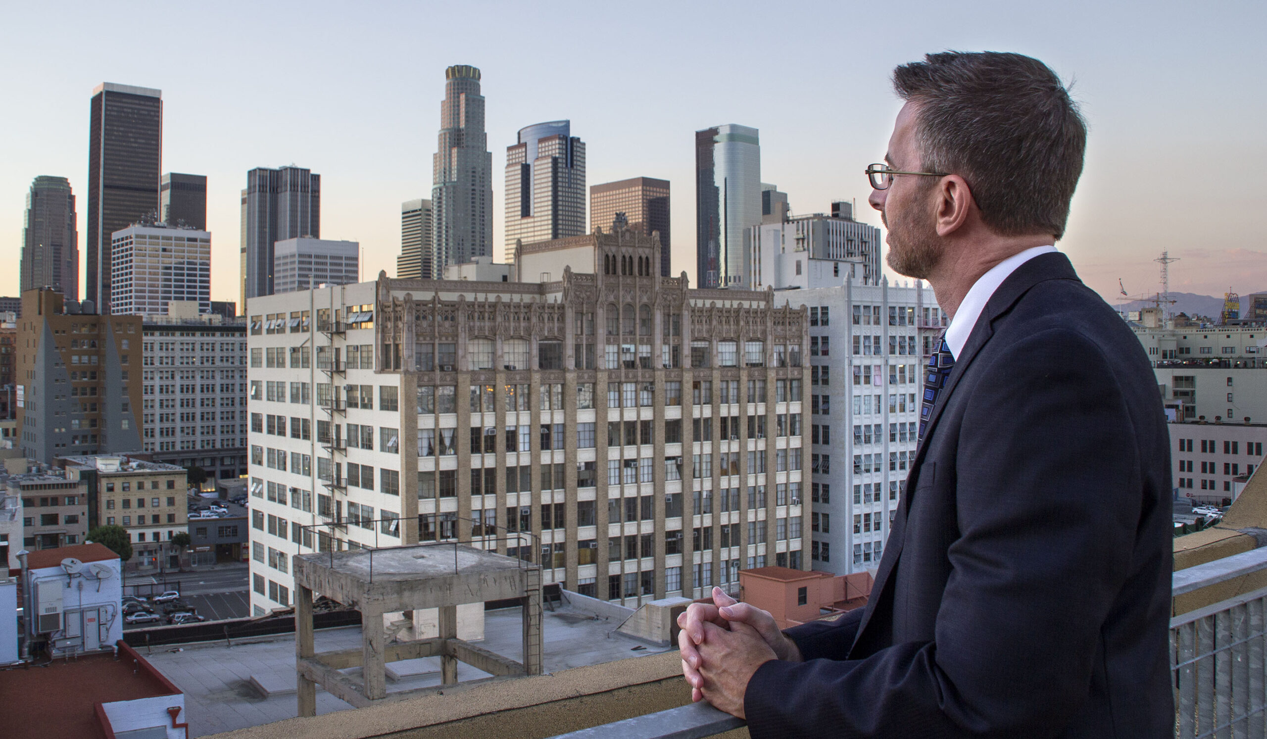 Condominium manager looking at the city skyline. The man is dressed in a suit. The view is during blue hour after sunset at the historic core of the city.