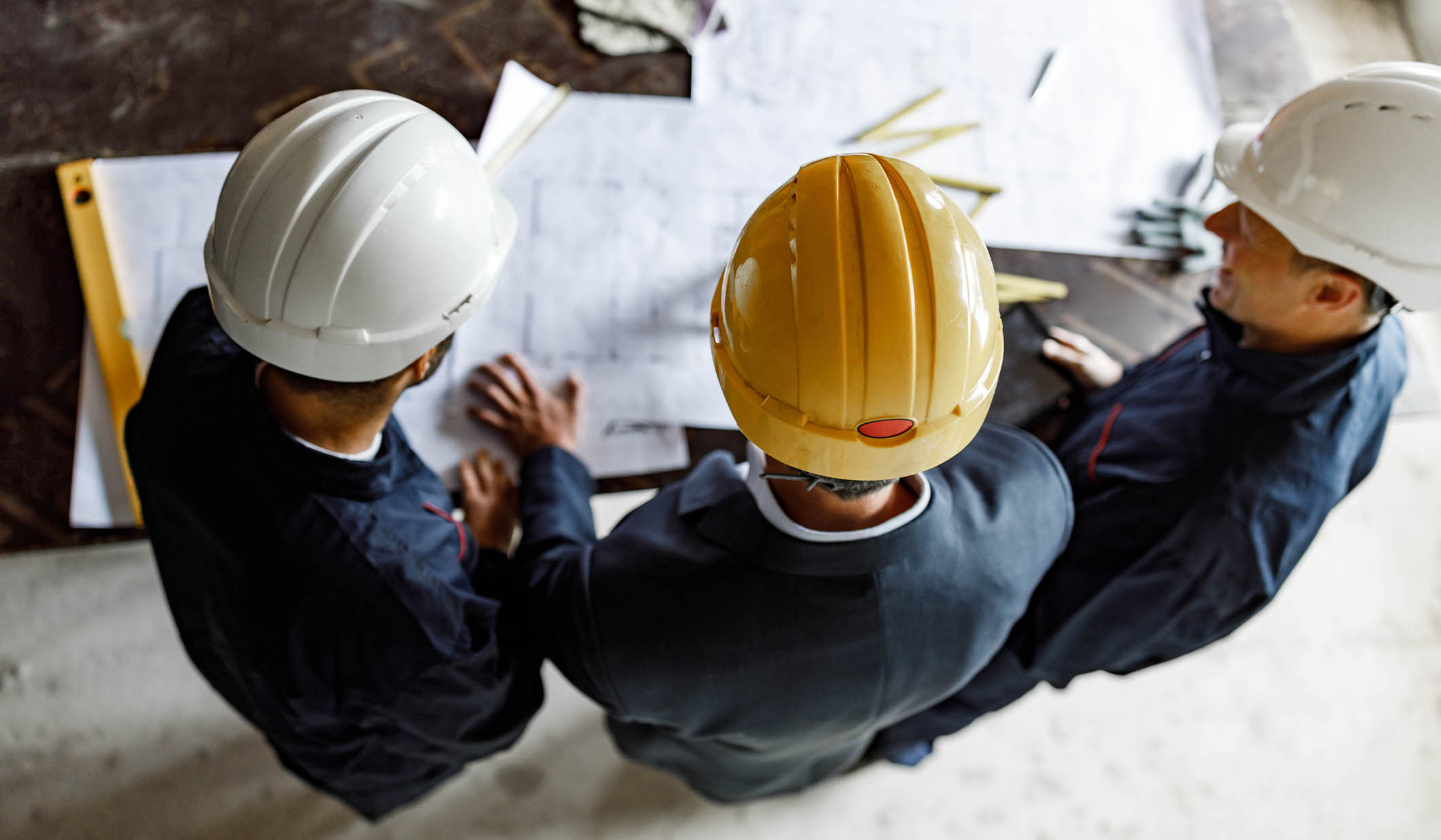 High angle view of manual workers and their foreman analyzing blueprints at construction site.