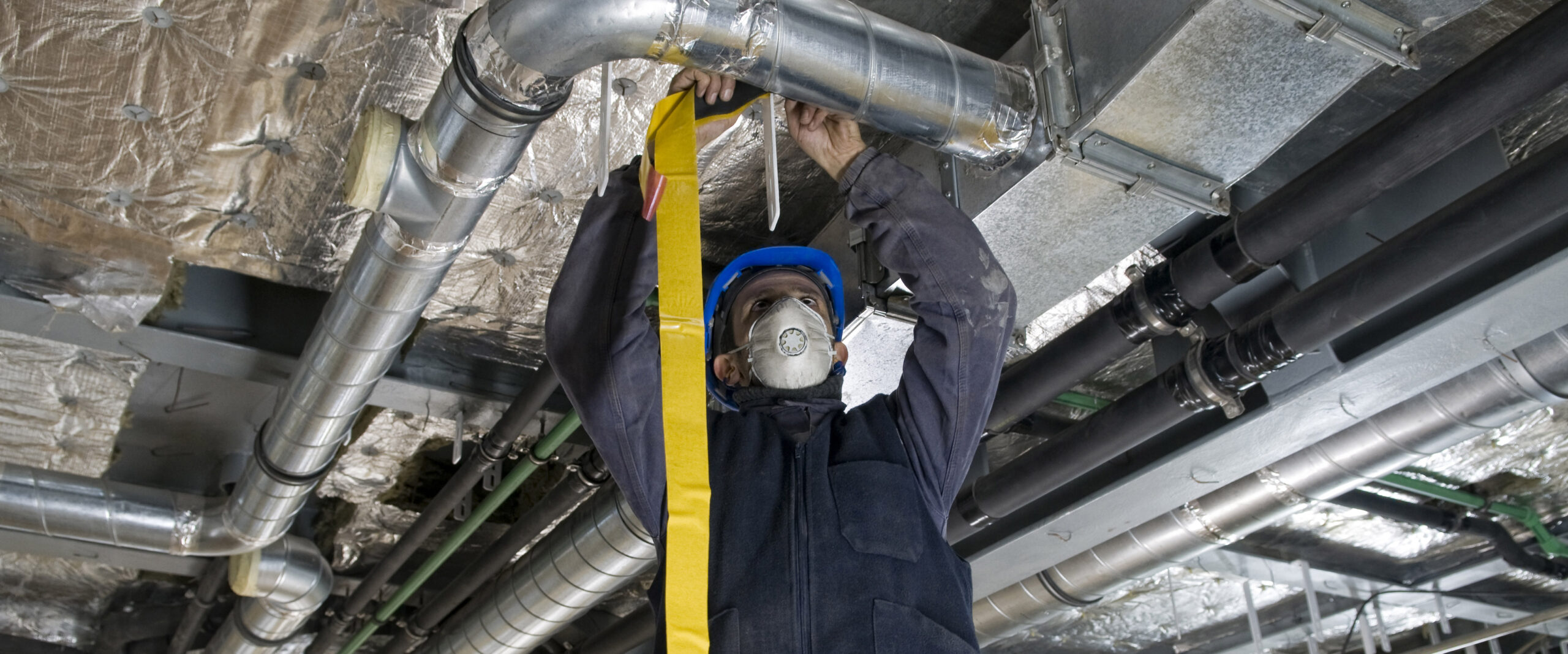 Worker Wrapping an HVAC Air Duct with Foil Tape
