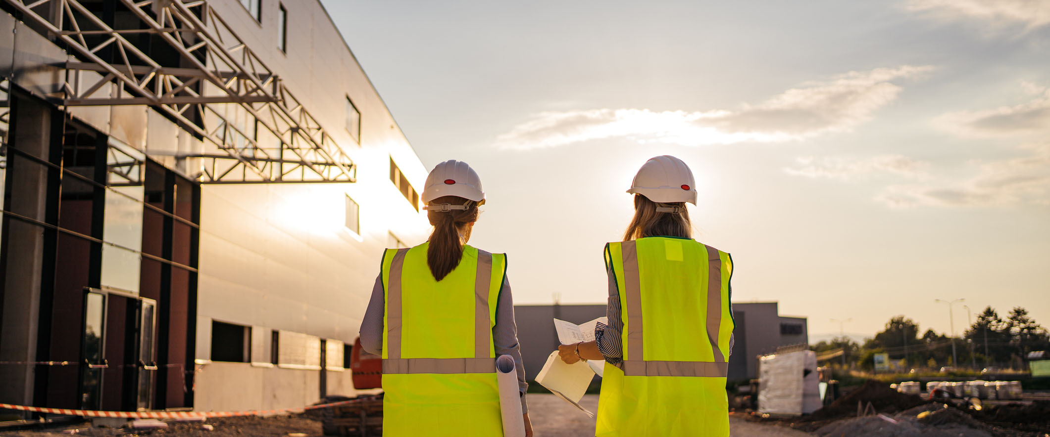Female construction engineers with helmet walking through the construction site and making plans for their project.